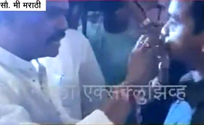 Video grab showing Shiv Sena's Thane MP Rajan Vichare force-feeding Arshad