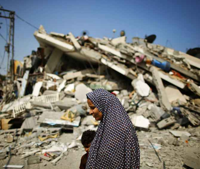 A Palestinian woman walks past the rubble of a residential building destroyed in an Israeli air strike in Gaza City.