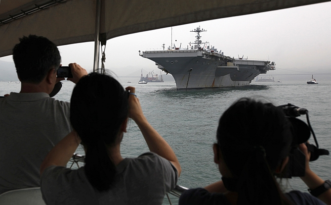 Journalists take photos of US aircraft carrier USS George Washington during its port call in the Hong Kong waters