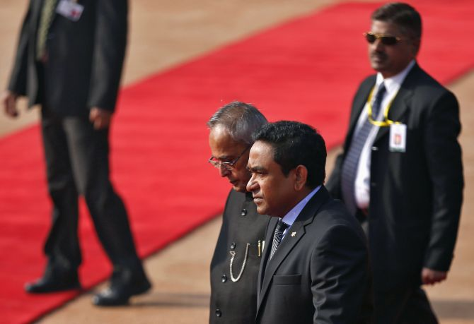 Maldives President Abdulla Yameen (2nd R) and his Indian counterpart Pranab Mukherjee (C), surrounded by security personnel, walk during Yameen's ceremonial reception at the forecourt of India's presidential palace Rashtrapati Bhavan in New Delhi January 2, 2014
