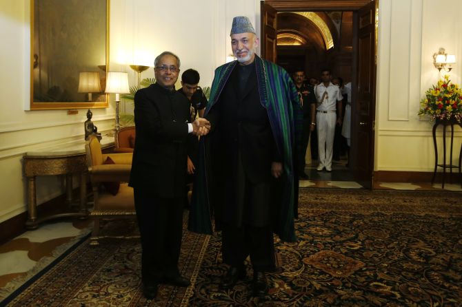 Afghanistan's President Hamid Karzai (R) shakes hands with his Indian counterpart Pranab Mukherjee ahead of their meeting at the Rashtrapati Bhavan presidential palace in New Delhi May 21, 2013