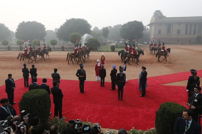 India's President Pranab Mukherjee (C) and India's the prime minister Manmohan Singh (blue turban) wait to receive South Korean President Park Geun-Hye during a ceremonial reception at the forecourt of India's presidential palace Rashtrapati Bhavan in New Delhi
