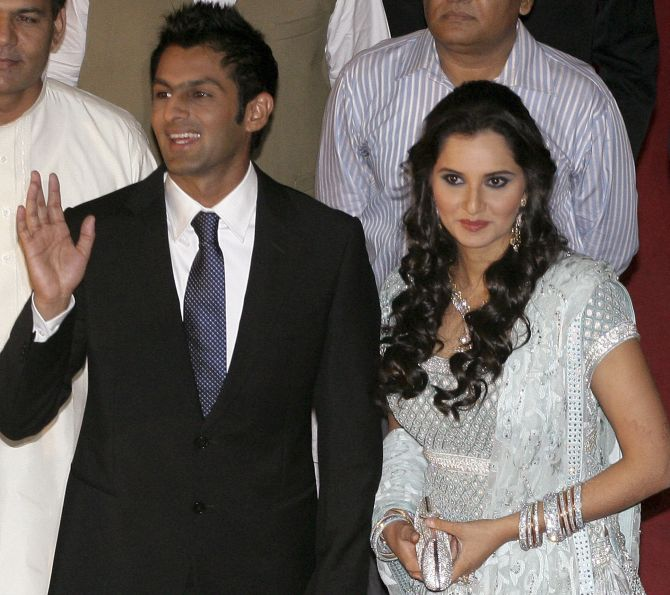 Pakistani cricketer Shoaib Malik with his wife, Indian tennis stars Sania Mirza, as they pose for photographs during their wedding reception in Lahore