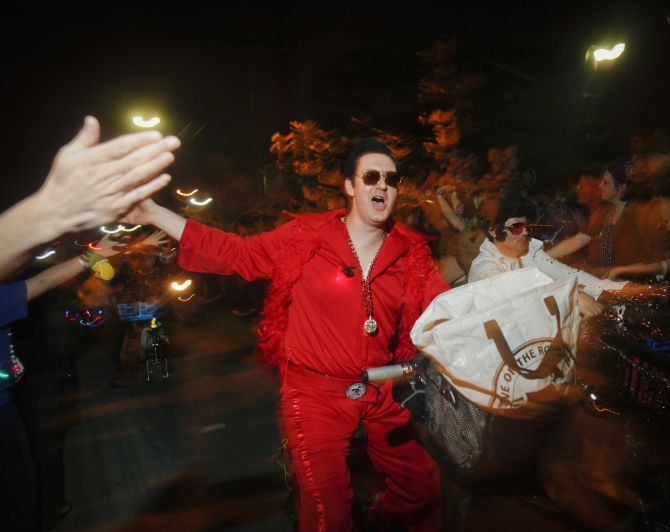 A member of the Krewe of Rolling Elvi, a local group who loves to dressed as Elvis Presley, rides a motorbike.