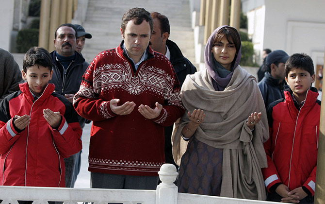 Omar Abdullah, president of the National Conference, prays with his two sons and his wife while standing beside the grave of Sheikh Mohammed Abdullah, his grandfather, in Hazratbal on the outskirts of Srinagar.