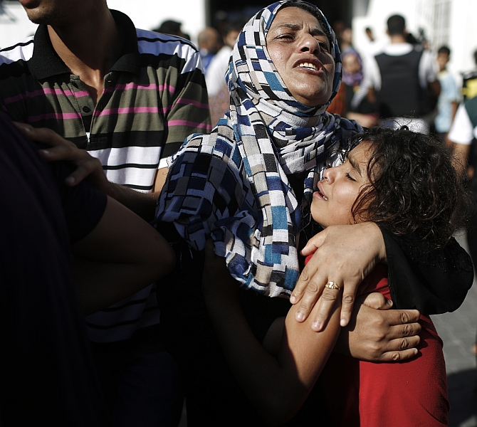 A Palestinian mother comforts her child after what medics said was an Israeli shell that hit a the school sheltering Palestinian refugees, at a hospital in Jabaliya in the northern Gaza