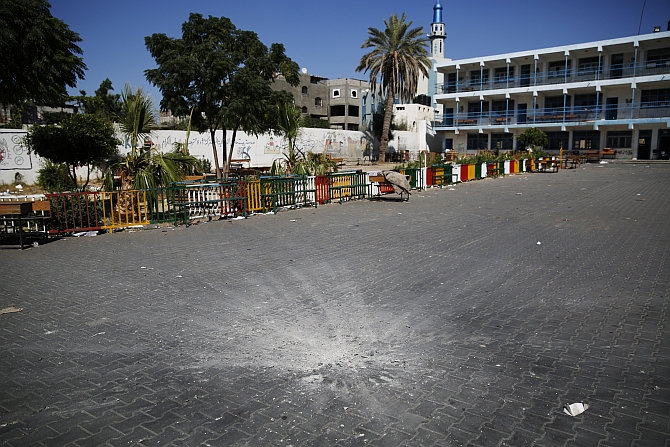 A crater marks the centre of a courtyard at a UN-run school sheltering Palestinians displaced by an Israeli ground offensive, that police said was hit by an Israeli shell, in Beit Hanoun in the northern Gaza Strip