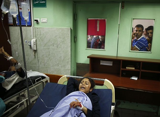 A Palestinian girl wounded in the school lies in a hospital bed