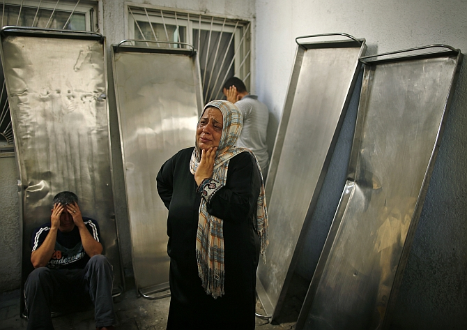 Relatives of Palestinians, whom medics said were killed in Israeli shelling, mourn outside the hospital morgue