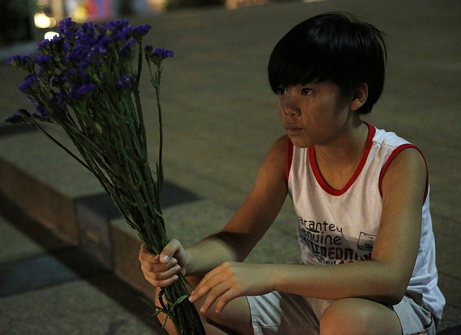 A boy waits to place flowers at a vigil for victims of Malaysia Airlines Flight MH17 in Kuala Lumpur.