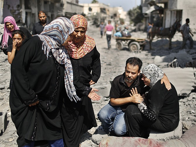 A Palestinian man comforts his relative as she sits next to her destroyed house in Beit Hanoun town, which witnesses said was heavily hit by Israeli shelling and air strikes during Israeli offensive, in the northern Gaza Strip