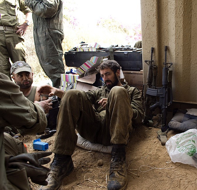 Israeli soldiers relax in the shade outside the northern Gaza Strip
