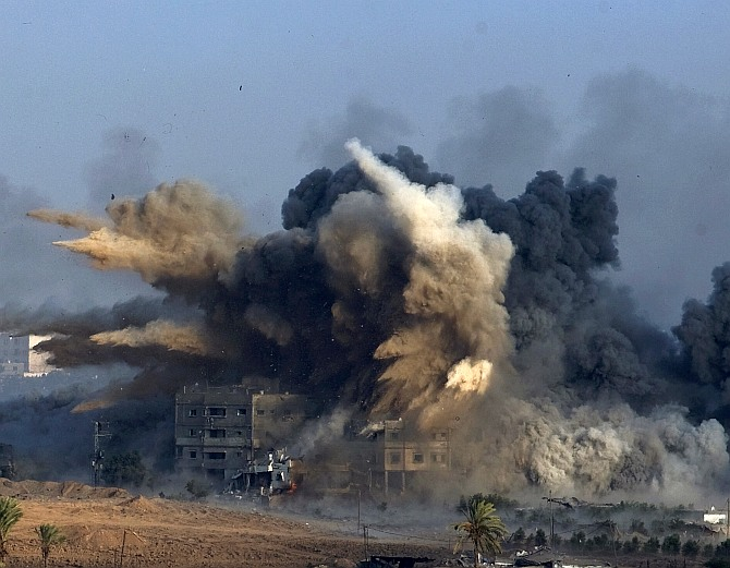 An explosion during an Israeli strike in the northern Gaza Strip is pictured from the Israeli border with Gaza, early morning July 26
