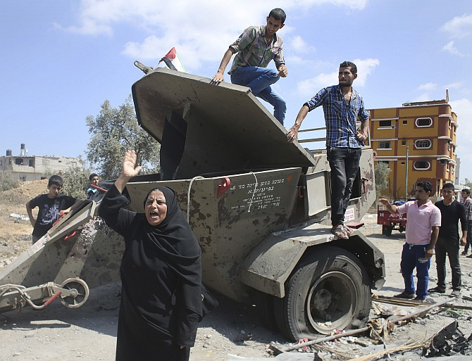 A Palestinian woman gestures in front of an Israeli military equipment, which witnesses said left behind by Israeli forces during a ground offensive, east of Khan Younis in the southern Gaza Strip July 26