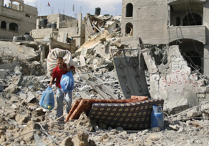 A Palestinian man carries his belongings from his destroyed house in Beit Hanoun town, which witnesses said was heavily hit by Israeli shelling and air strikes during Israeli offensive, in the northern Gaza Strip July 26