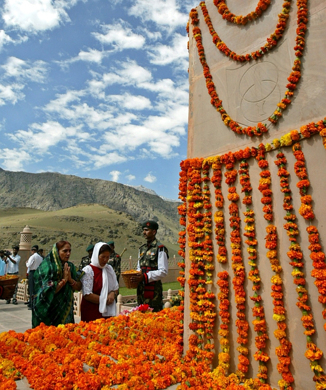 Relatives of Indian soldiers killed in a war with Pakistan pray in front a war memorial during 'Vijay Diwas' celebrations in Drass 1