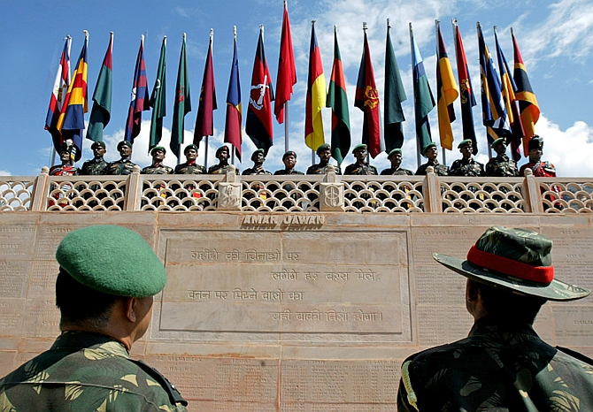 Senior Indian army officers look at a wall with names of killed colleagues as soldiers stand under their regimental flags during during 'Vijay Diwas' celebrations in Drass