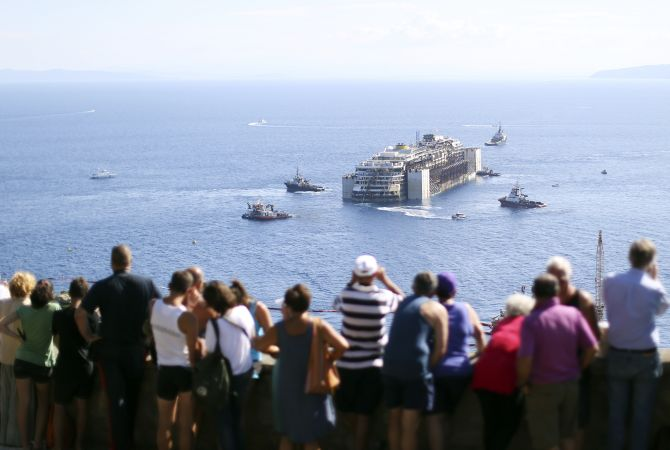 People watch the cruise liner Costa Concordia moving anticlockwise during the refloat operation maneuvers at Giglio Island.