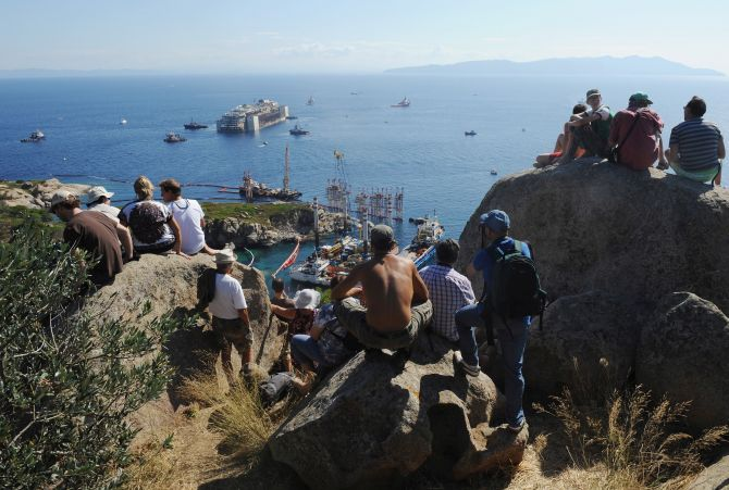 People watch as the wrecked cruise ship Costa Concordia is towed by tugs from Giglio after being refloated.