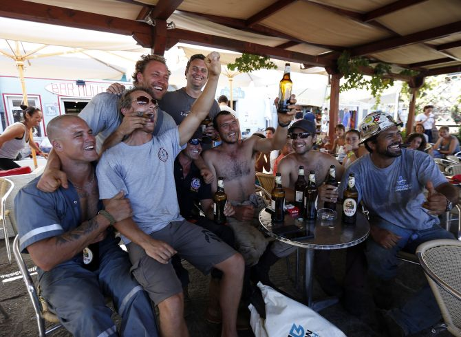 Dutch salvage workers celebrate after the refloat operation maneuvers that allowed cruise liner Costa Concordia to leave Giglio Island.