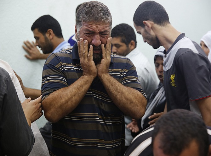 A Palestinian man mourns a relative who medics said died in Israeli shelling during an Israeli ground offensive, at the hospital morgue in Beit Lahita in the northern Gaza Strip July 30