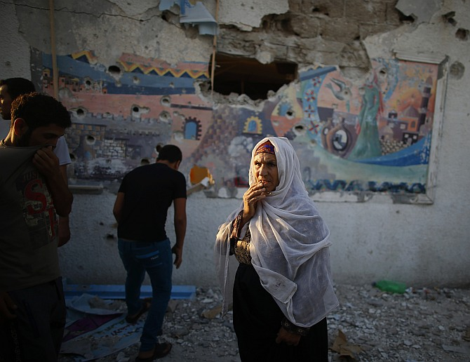 A Palestinian woman looks on as she stands at a United Nations-run school sheltering Palestinians displaced by an Israeli ground offensive, that witnesses said was hit by Israeli shelling, in Jebalya refugee camp in the northern Gaza Strip