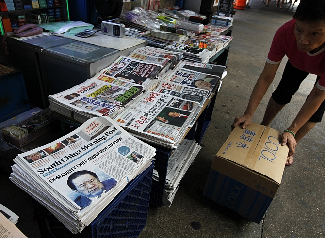 A vendor works beside Hong Kong newspapers showing photos of China's then Politburo Standing Committee Member Zhou Yongkang displayed at a newsstand in Hong Kong