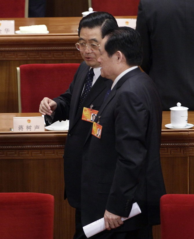 Zhou Yongkang talks with former China's President Hu Jintao after a plenary session of the National People's Congress at the Great Hall of the People, in Beijing