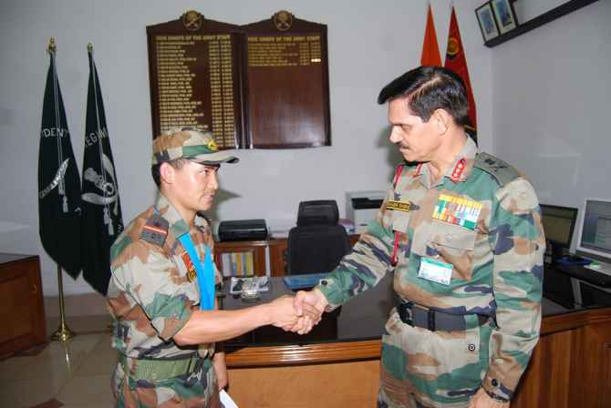 Lt General Singh felicitating a young soldier for his bravery