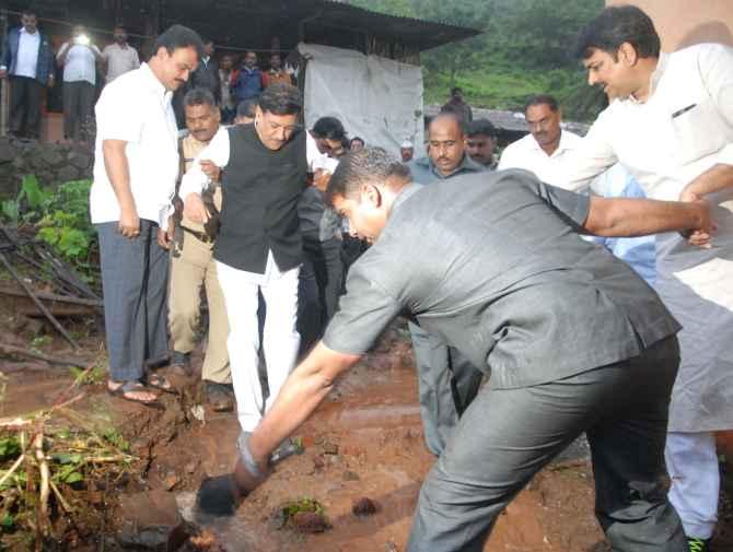 Maharashtra CM Prithviraj Chavan makes his way through the slush at the site of a landlside near Pune on Wednesday