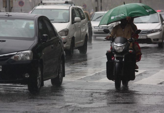 A pillion rider tries to shield himself from the heavy downpour in Mumbai