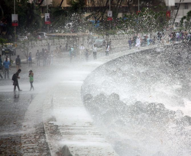 Two children enjoy the waves of the water lashing against the rocks at Marine Drive on Tuesday.