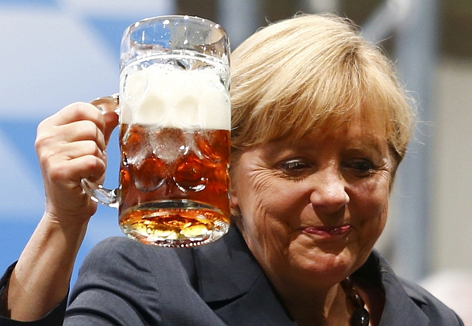 German Chancellor Angela Merkel toasts with beer after her speech in Dachau near Munich