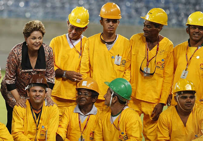 Brazil President Dilma Rousseff poses with workers during the opening ceremony of the Arena das Dunas stadium