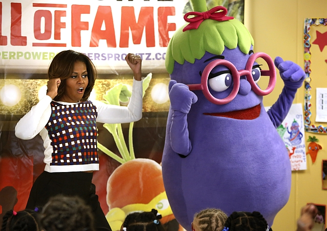 US First Lady Michelle Obama dances with an eggplant from the Super Sprowtz at a La Petite Academy chid care center in Bowie, Maryland