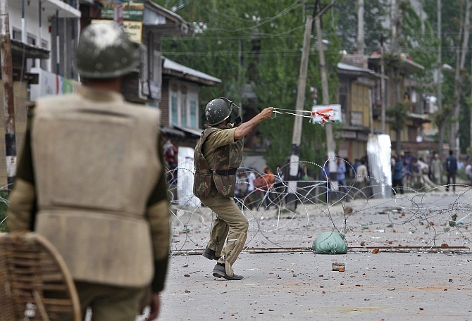 A policeman throws a stone towards Kashmiri protesters during an anti-election protest in Baramulla district, north of Srinagar