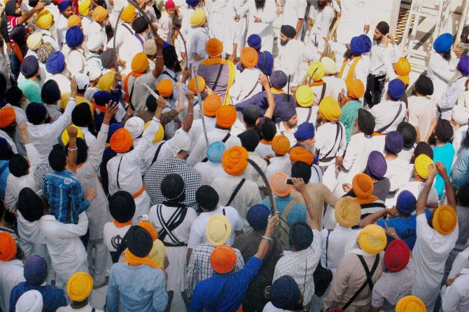 Sikh men brandishing swords during a clash between SGPC supporters and a radical Sikh organisation on the 30th anniversary of Operation Bluestar, at Golden Temple Complex in Amritsar