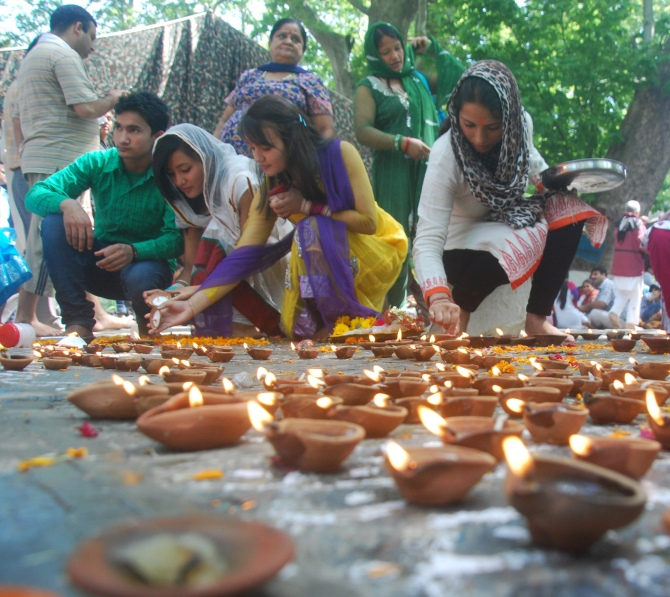 Devotees lighting earthen lamps during the Kheer Bhawani mela