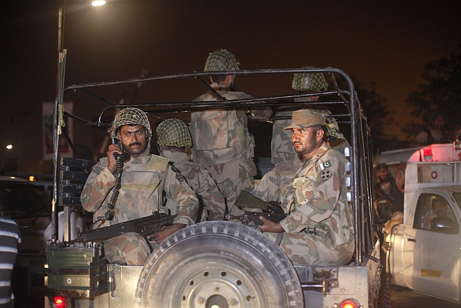 Pakistan army soldiers sit on a vehicle as they arrive at Jinnah International Airport in Karachi