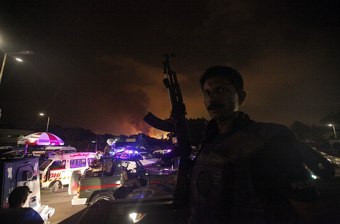 A policeman with a gun stands guard on a vehicle as smoke billows from Jinnah International Airport in Karachi