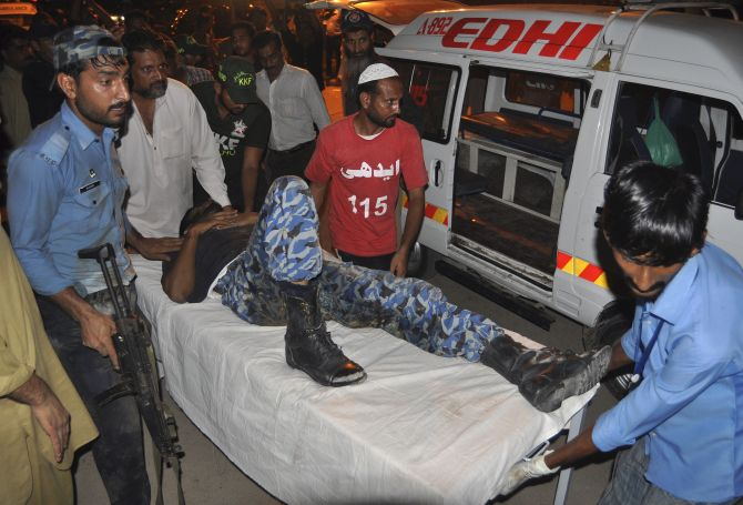 An Airport Security Force soldier (L) leads a colleague on a stretcher, who was wounded in an attack at Jinnah International Airport, outside Jinnah hospital in Karachi