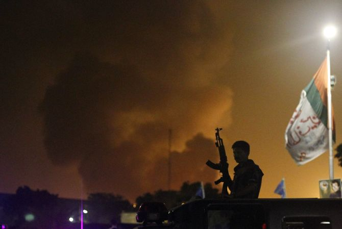 A gunman stands guard as smoke billows from Jinnah International airport.