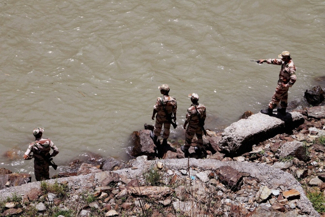 NDRF personnel carry out a rescue operation in Beas River near Pandoh Dam in Mandi on Monday