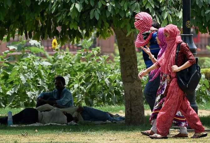 Students walking with their heads covered while others take rest under a tree on a hot day in Delhi