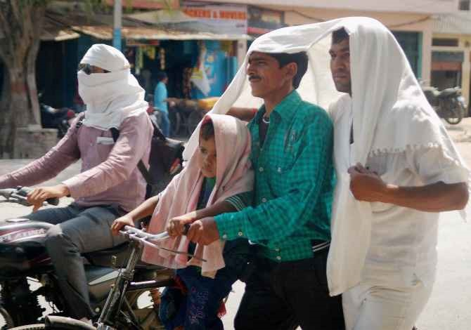 Men cover their heads to protect themselves from the sorching heat in Varanasi, Uttar Pradesh