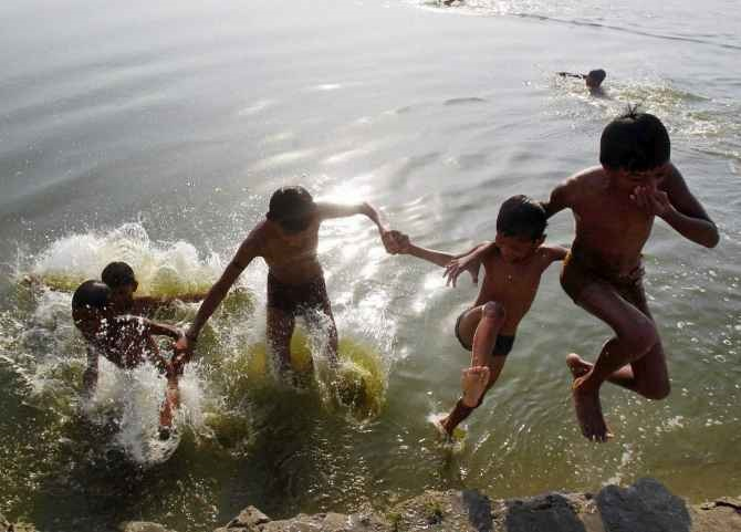 Boys take a splash in the Ganga on a hot day in Allahabad