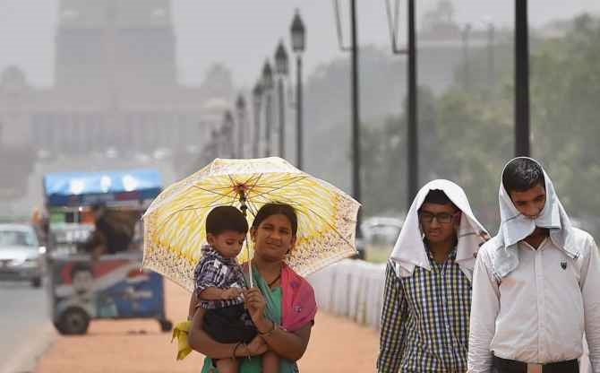 People take protection from the scorching heat on a hot day at Rajpath in New Delhi