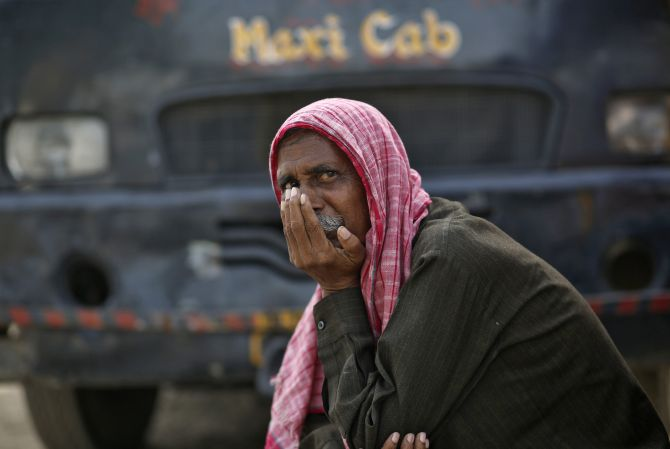 A passenger waits to board a bus at a bus stop on a hot summer day in the old quarters of Delhi