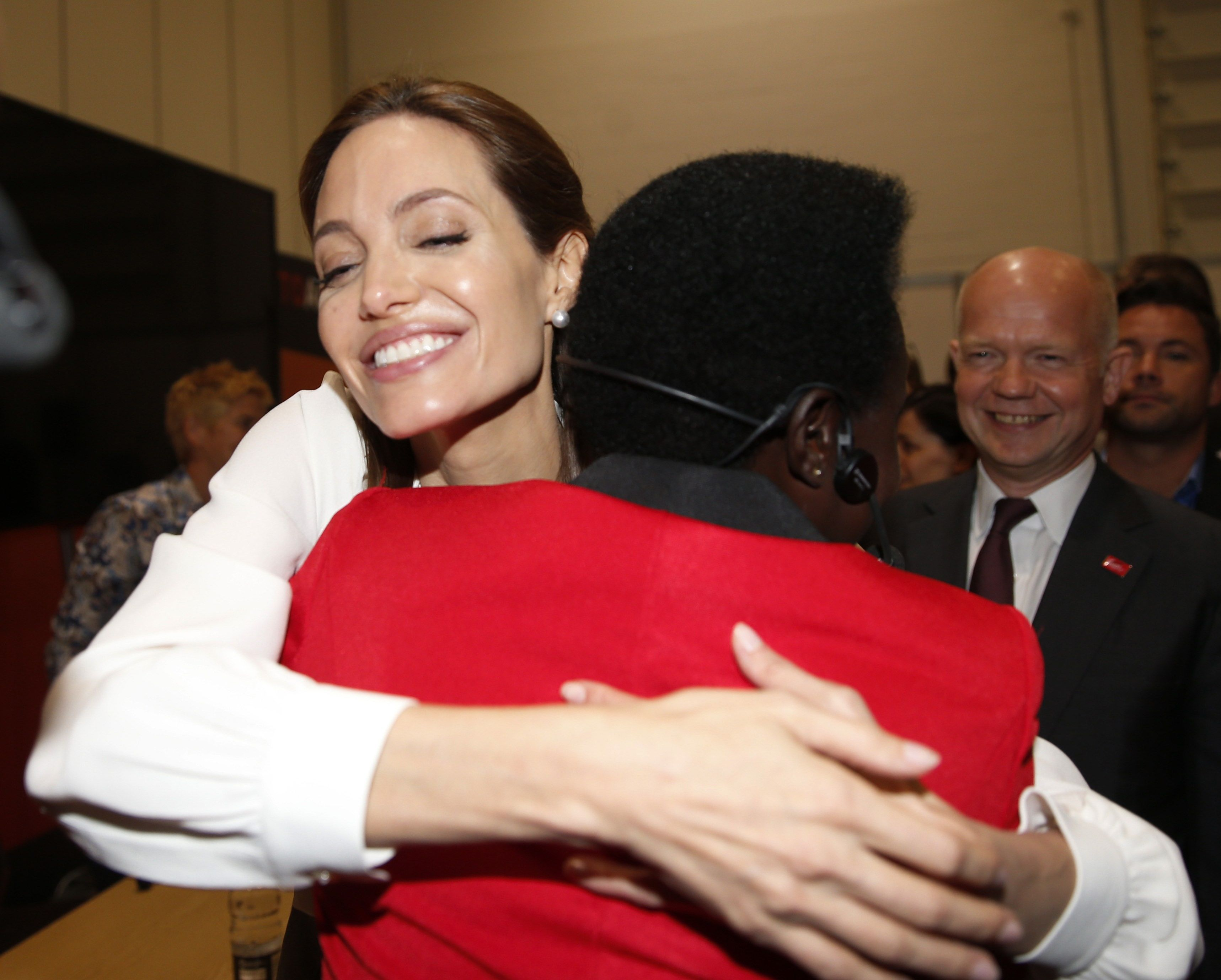 Jolie embraces Esther Ruth Atim of Uganda, at the 'End Sexual Violence in Conflict' summit