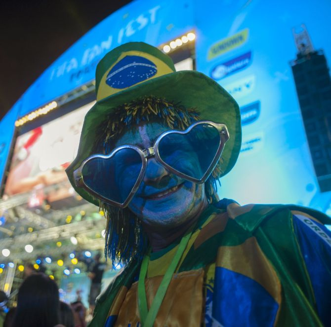 A fan dresses in the colours of the Brazilian flag hours before the World Cup kicks off.